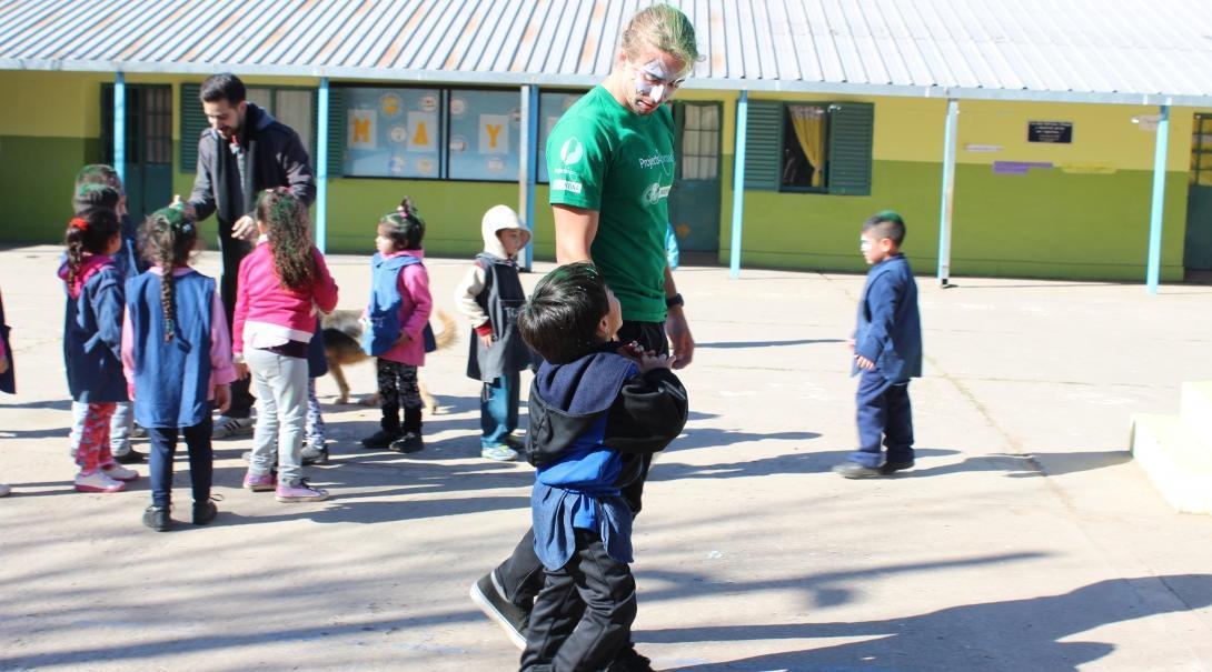 Un niño hablando con un voluntario social durante una actividad al aire libre en un preescolar argentino.